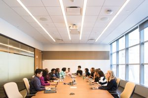 people having meeting on rectangular brown table